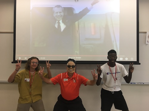 Alex Ladd, teacher Dennis Johnson, and Malik Mulder make Nixon fingers and one wears a Nixon mask under a photo of him boarding the helicopter after he resigned.